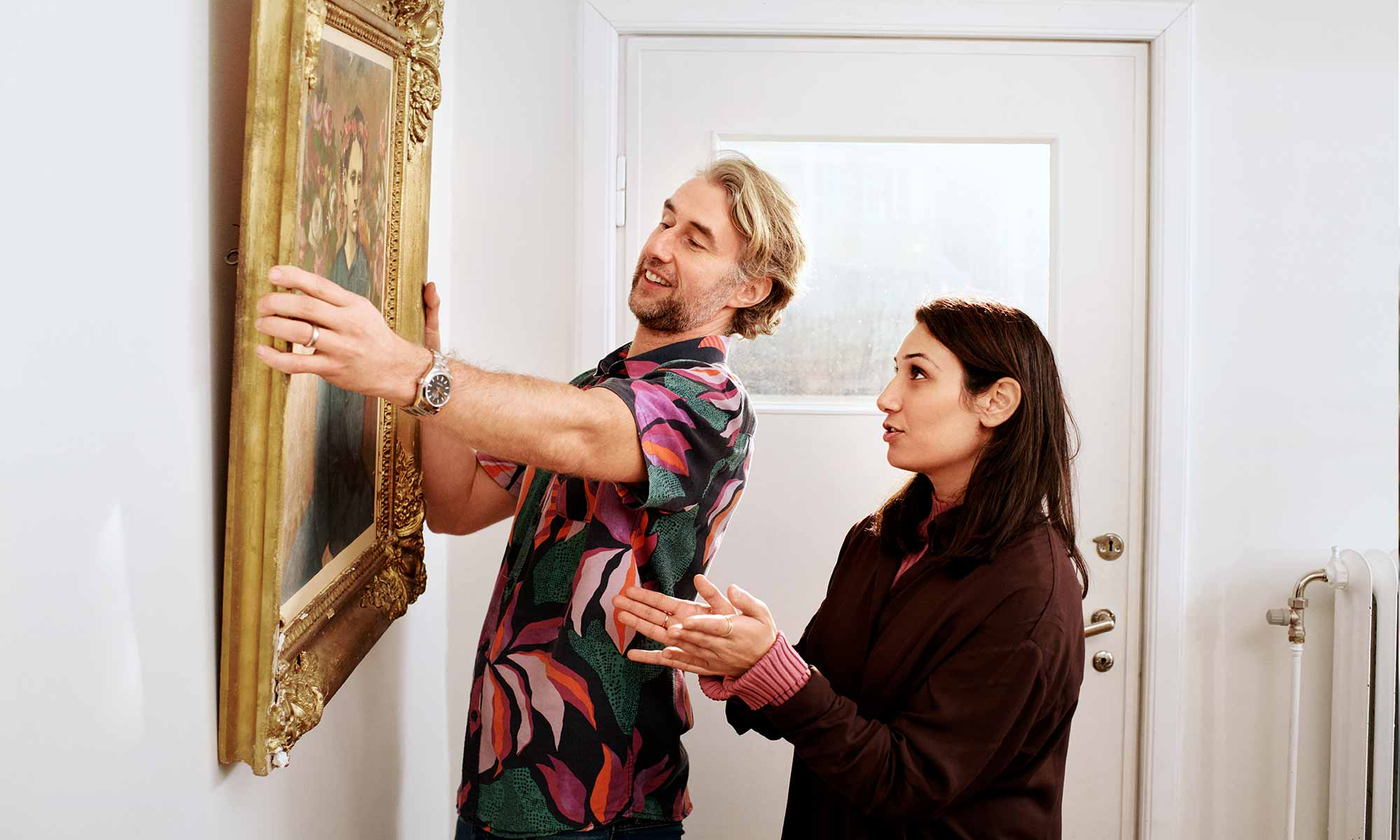 Couple hanging a painting on the wall